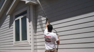 Vivax Pro worker pressure washing siding of house