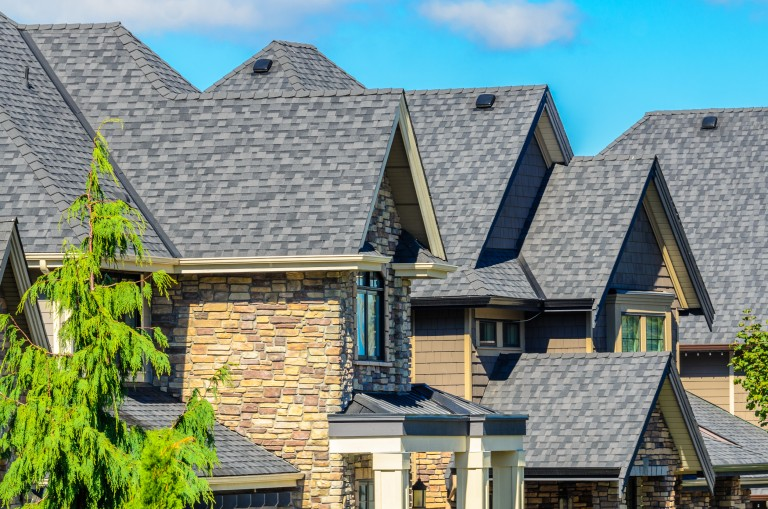Stone townhomes with grey asphalt roofing