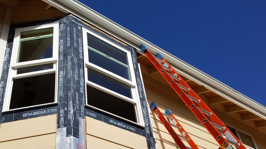 Window being installed on tan house