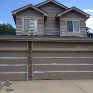 Painter taping off garage doors for new paint