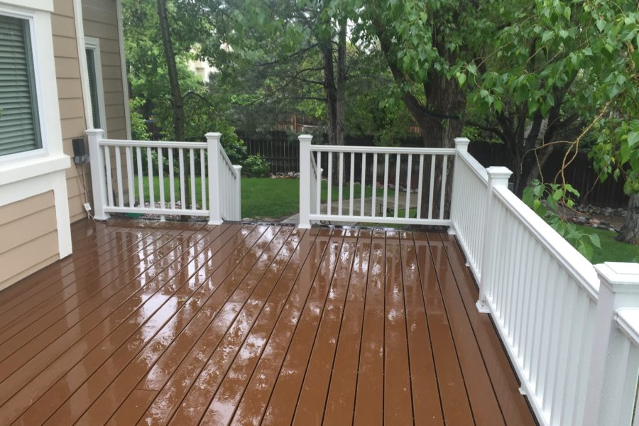Brown deck with white railing and stairs