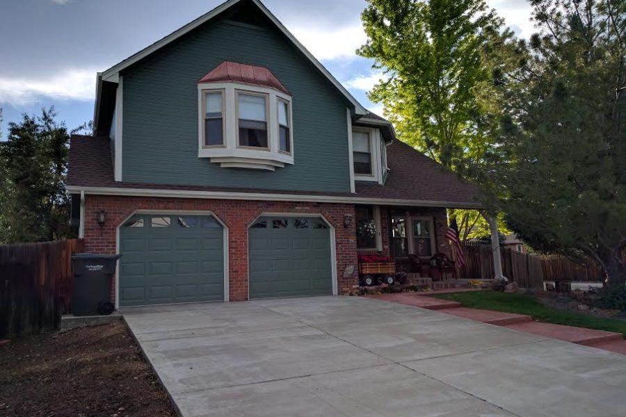 Dark green house with red brick garage