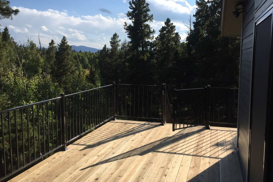 Natural wood deck with metal rails overlooking mountains