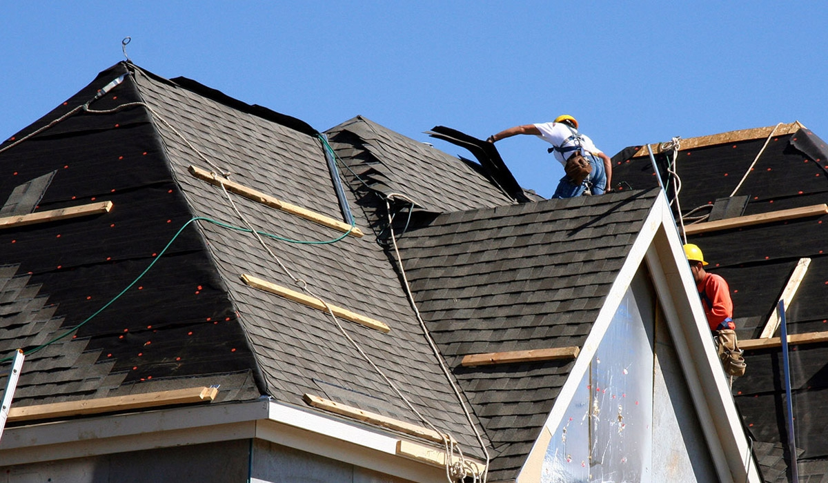 Roofers on top of house working